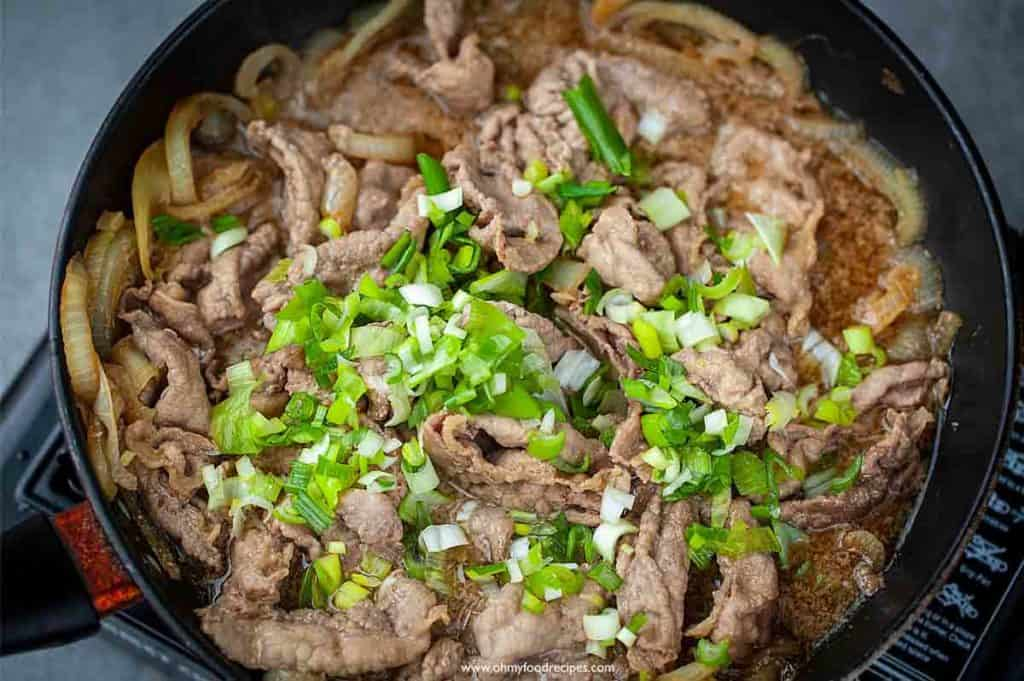 cooked beef gyudon in a pan with green onion on top