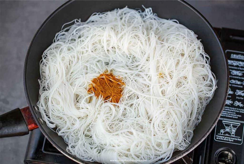 pan fry rice noodles in a pan add curry powder