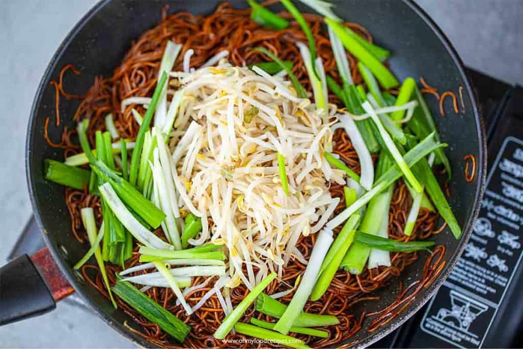 bean sprout noodles and green onion in a pan