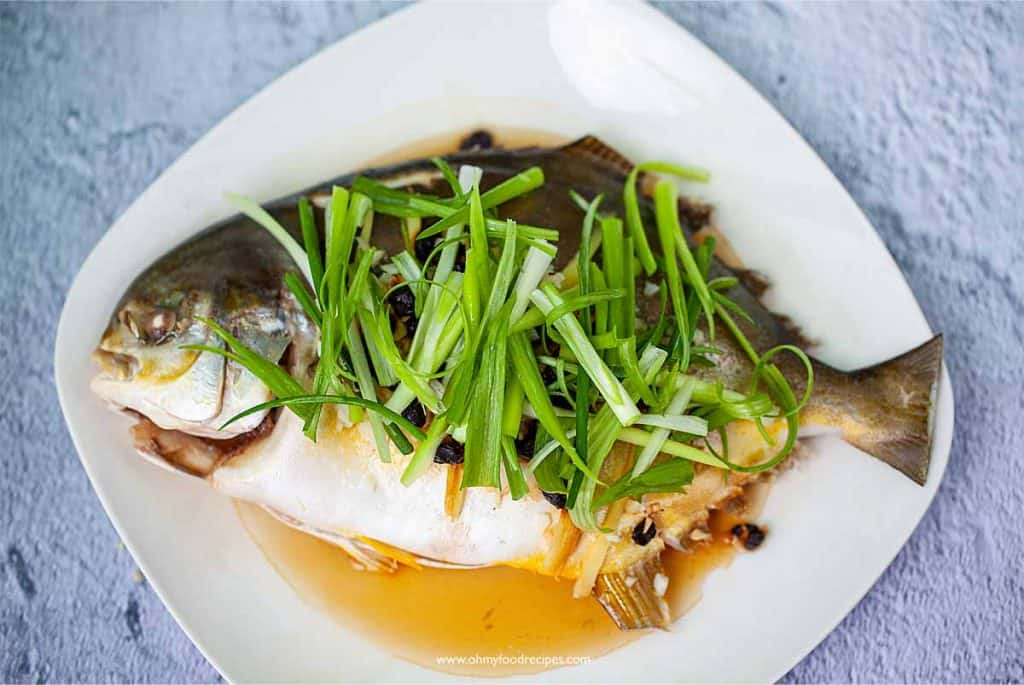 green onion lay on top of the cooked fish