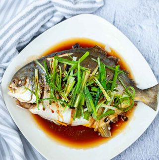 steamed a whole fish on a plate with a towel