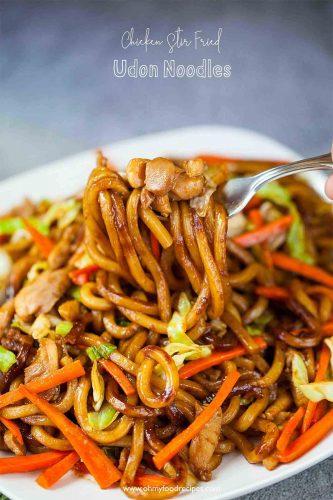 stir fry chicken udon noodles on a fork