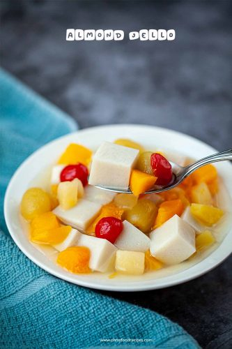 almond jelly with mixed canned fruit on a sliver spoon