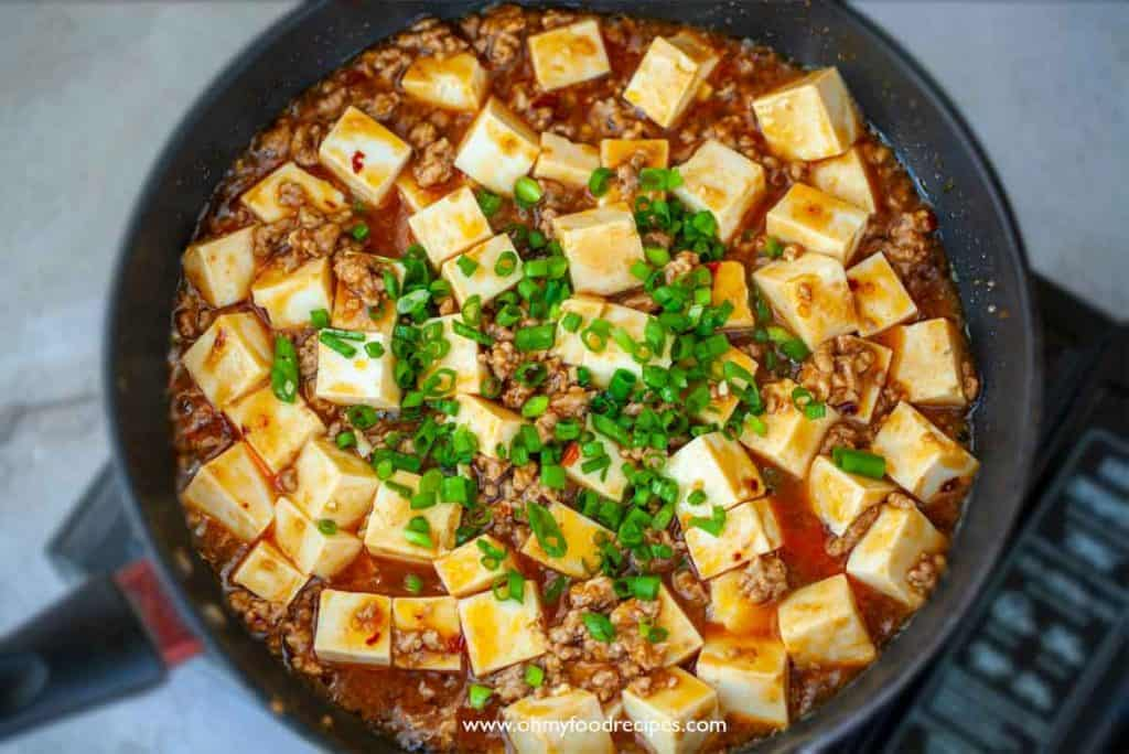 sprinkle green onion on mapo tofu in a pan