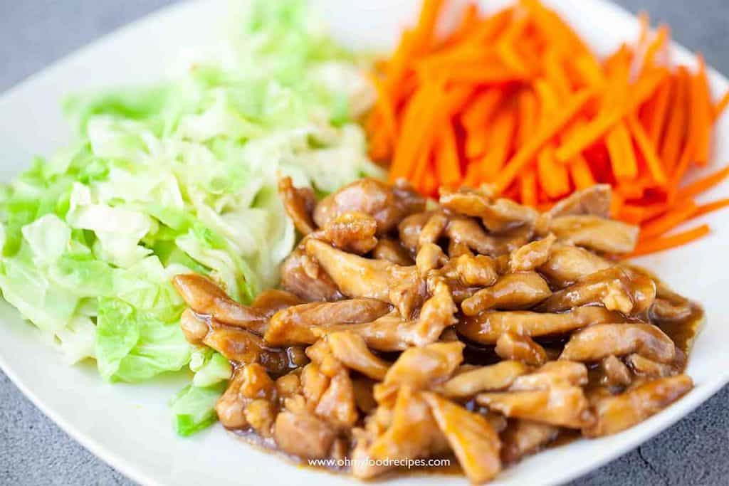 cooked carrot, cabbage and chicken on a white plate