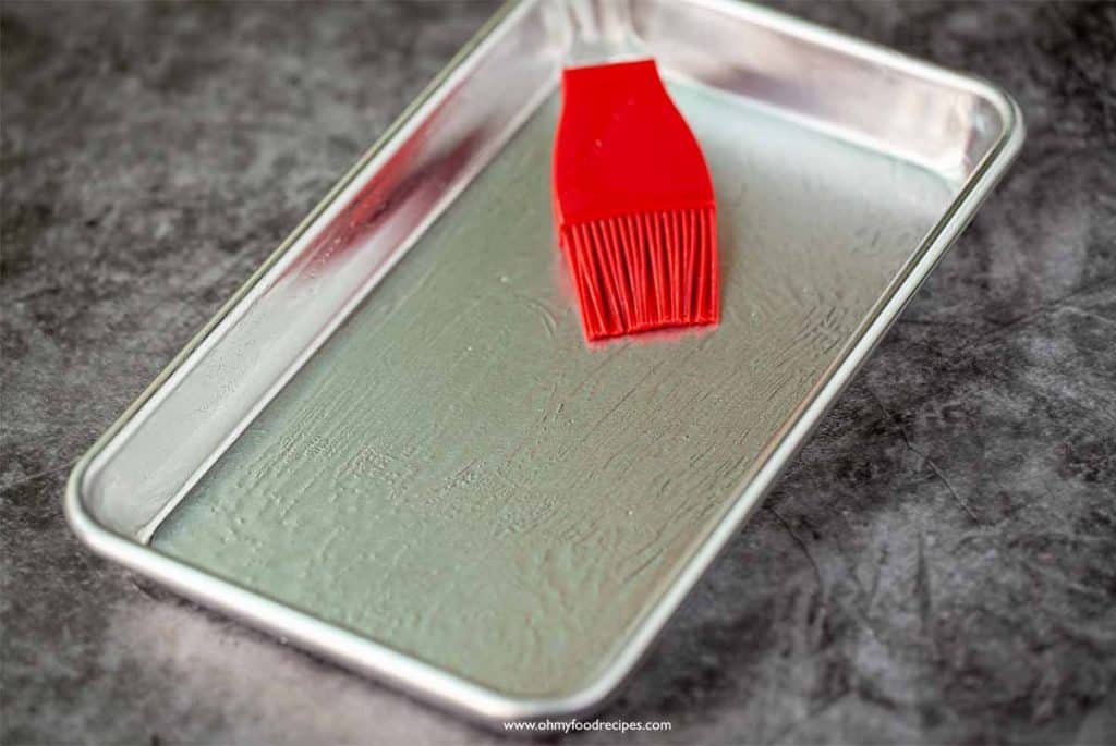 a red brush brushing oil on a tray