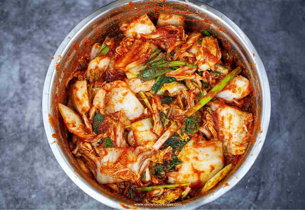 kimchi mixed with sauce in a sliver bowl