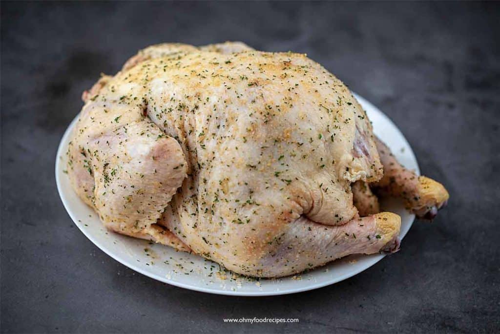 marinate whole chicken with seasoning on a plate