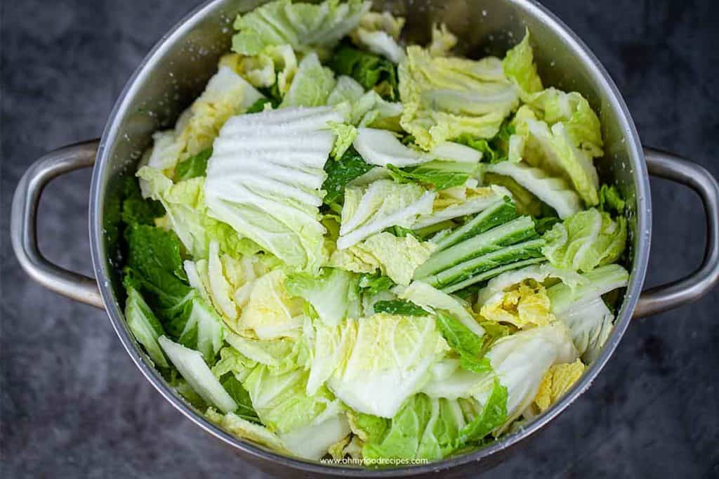 napa cabbage into a big sliver pot with salt on napa cabbage