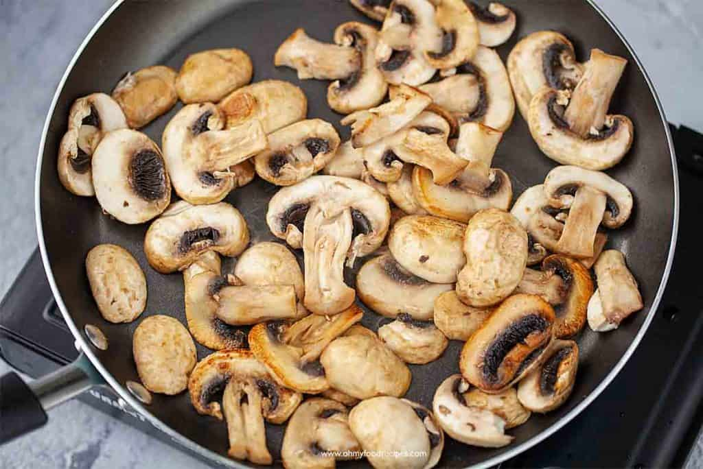 stir fry mushrooms in a pan