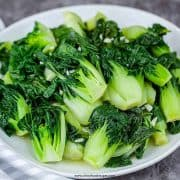 easy baby bok choy stir fry on a white plate with a stripe gray towel