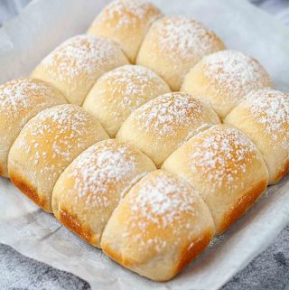 Baked Japanese milk bread rolls on parchment paper