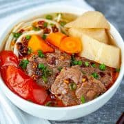 Taiwanese beef noodle soup with a striped towel and chopsticks