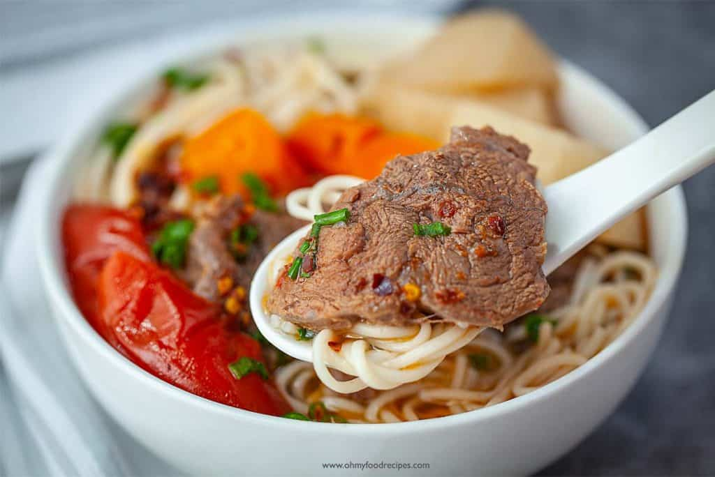 close up Taiwanese beef noodle soup noodle and beef on a spoon