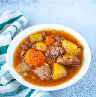beef stew in a white bowl with a striped towel on the side