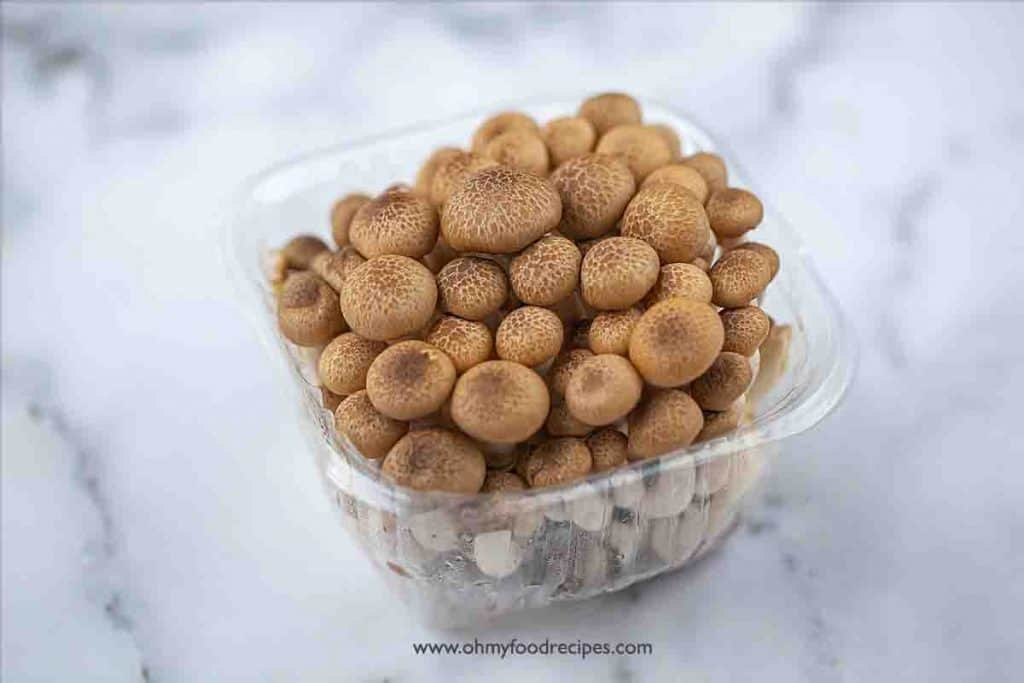 a pack of brown beech mushrooms in a plastic container