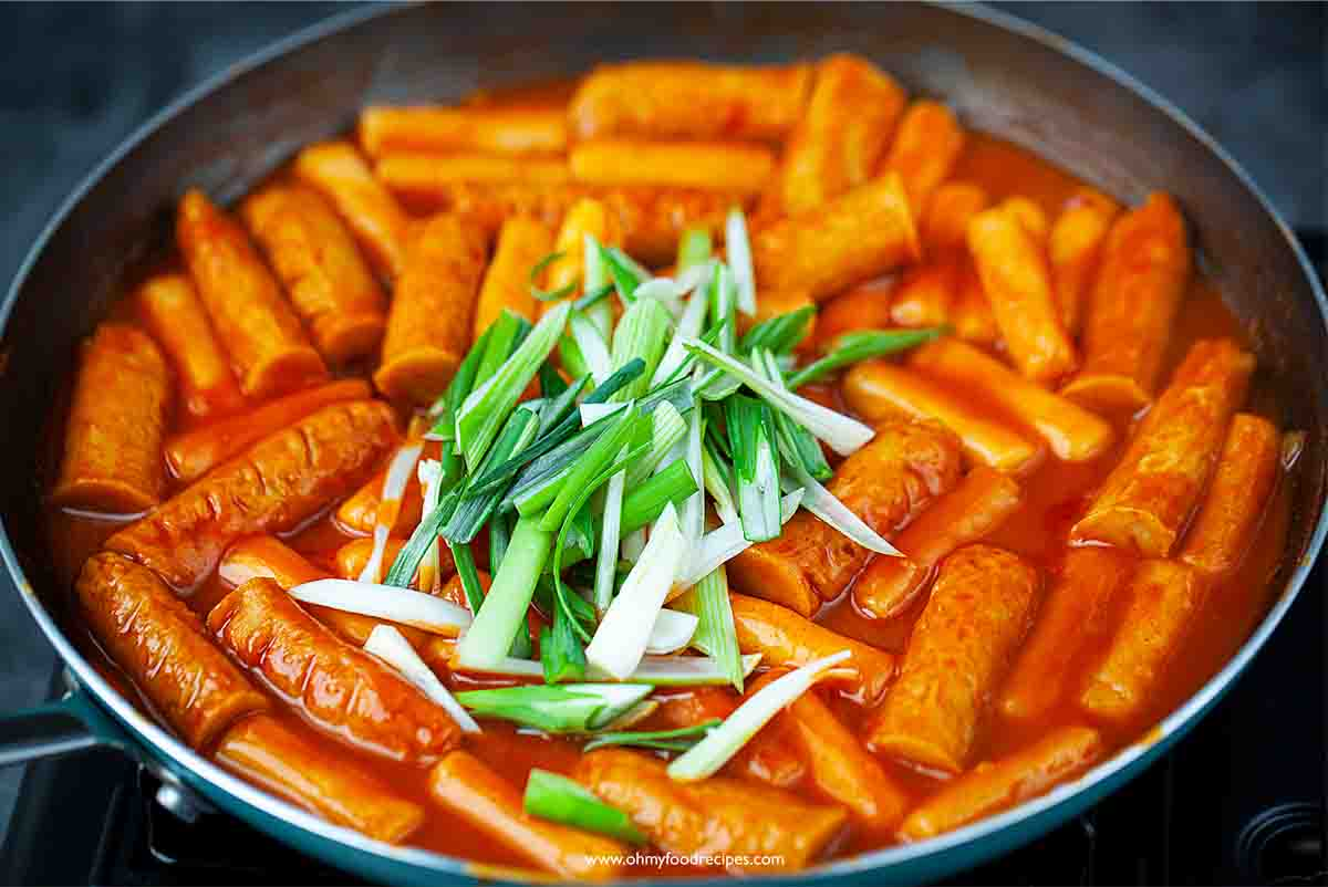 Green onion topping on tteokbokki Korean spicy rice cake in the pan