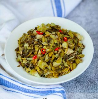 Chinese mustard greens stir fry in a white bowl with a blue striped towel