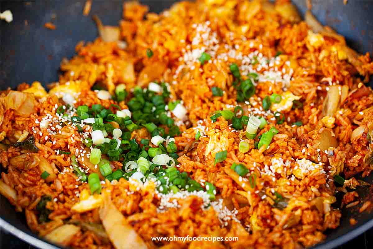 green onion and sesame seeds add into the kimchi fried rice in the wok