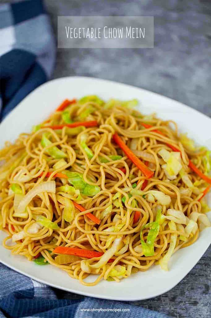 Chinese vegetable chow mein on a white plate with a blue white checked towel