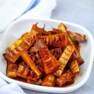 Chinese braised bamboo shoots on the white plate with a blue striped white towel