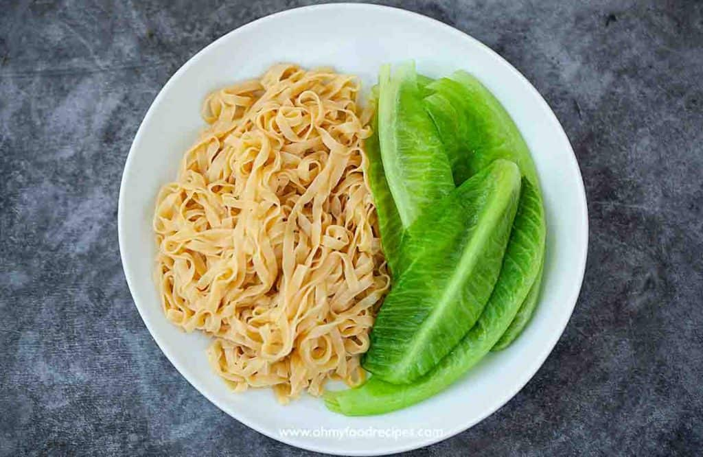 cooked wide fresh egg noodles and lettuce on the white plate