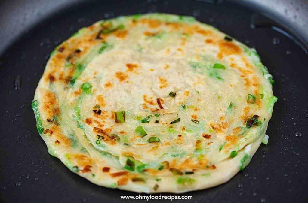 pan frying Chinese green onion scallion pancake in the pan