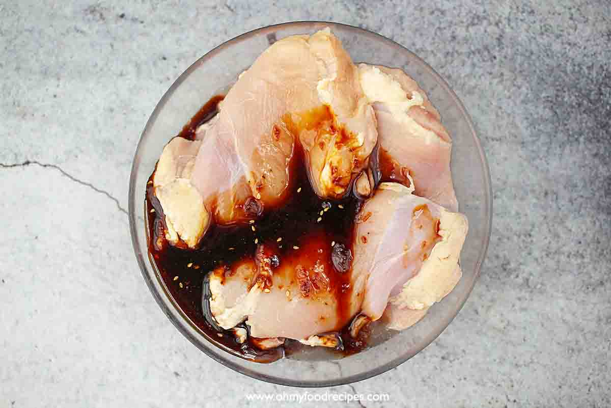 Teriyaki sauce pour over the chicken thighs in the glass container top view