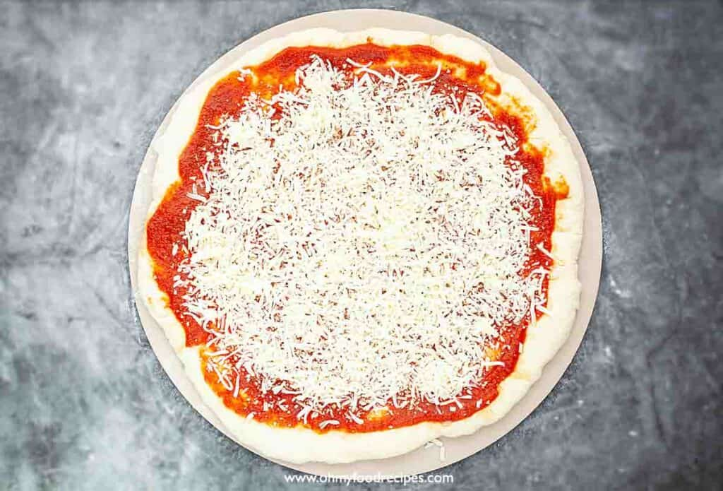 cheese topping unbaked pizza top view