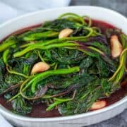 cooked red Chinese spinach in a white container