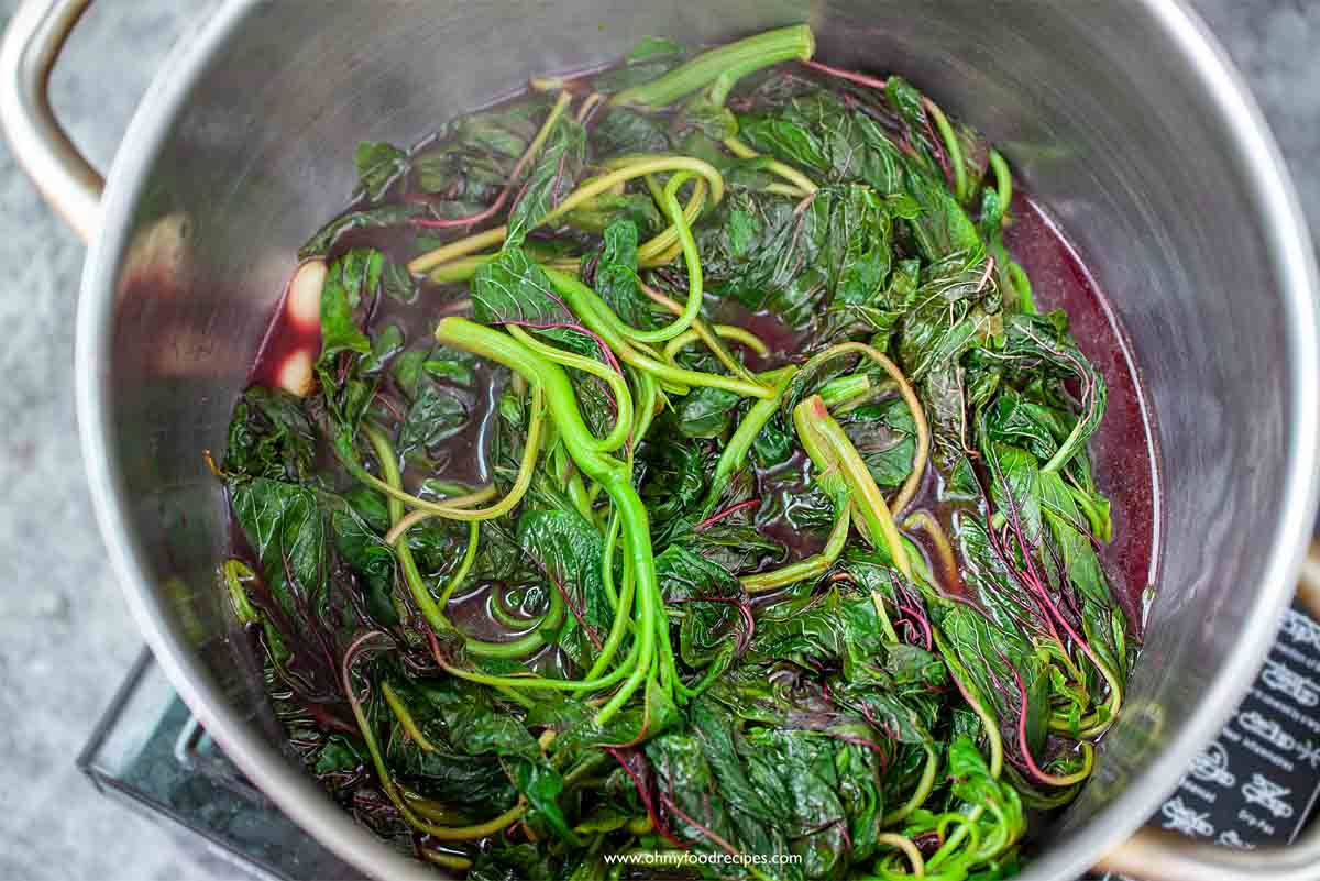 yin choy Chinese red spinach amaranth cooking in the sliver pot with garlic
