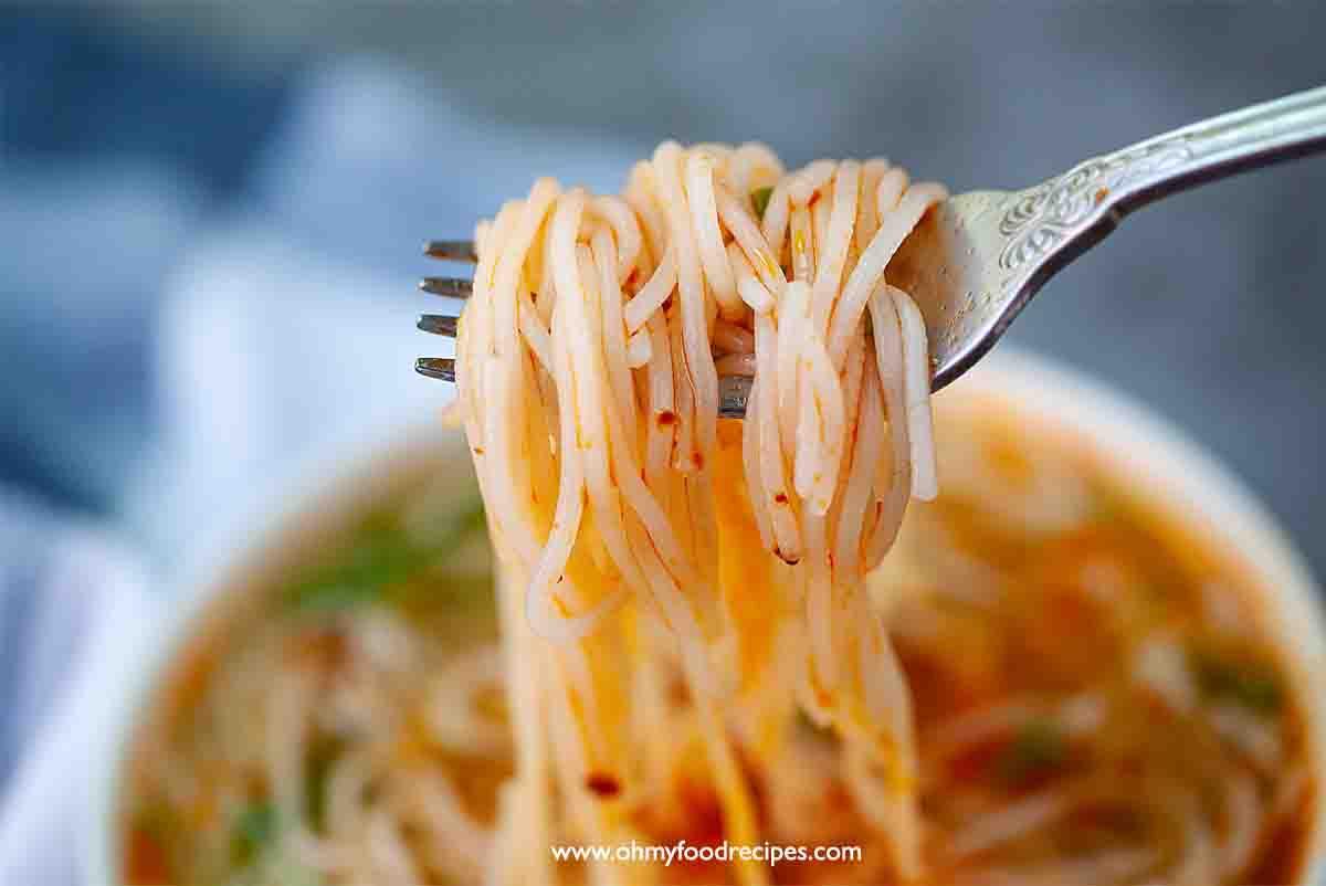 cooked homemade fresh rice noodles with chili oil on the fork close up