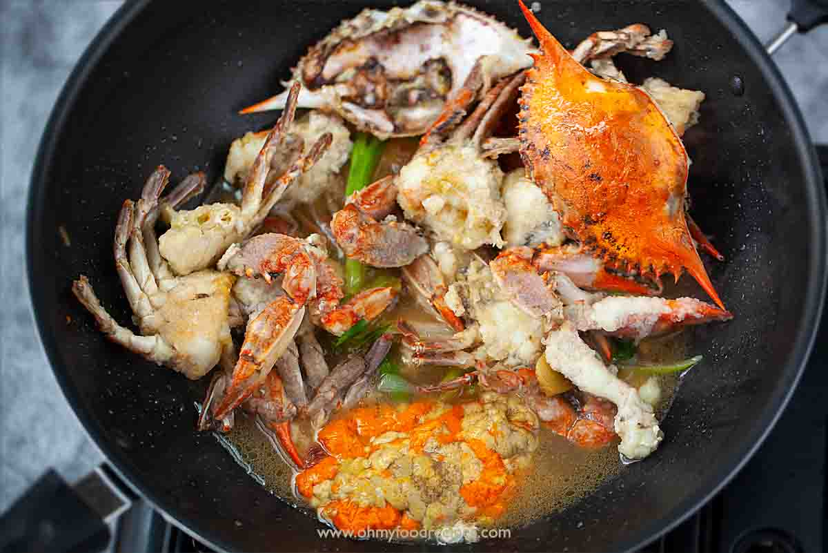 roe and fried crab stir fry in the wok with ginger scallion
