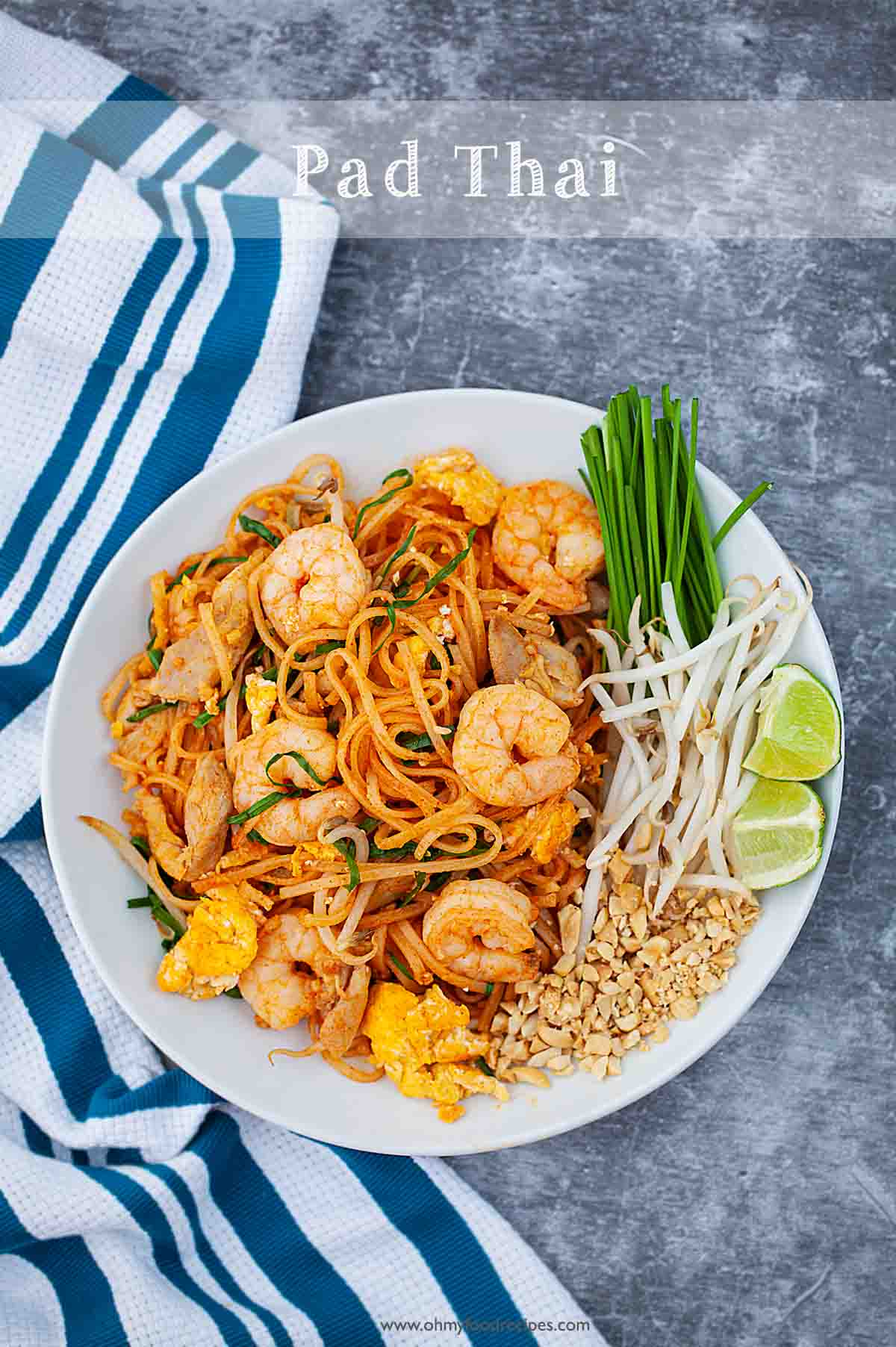 easy homemade stir fry pad thai noodles on the plate with blue striped towel as background