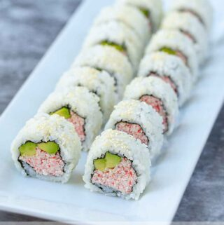 cut up homemade California sushi rolls on a white plate